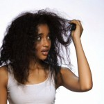 Young woman holding hair against white background